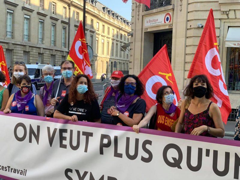zoom devant l'assemblée nationale militant.es derrière la banderole On veut plus qu'un symbole