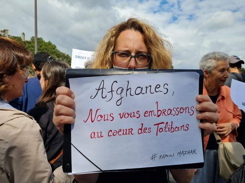 """militante avec une pancarte """"aghanes nous vous embrassons au coeur des Talibans"""