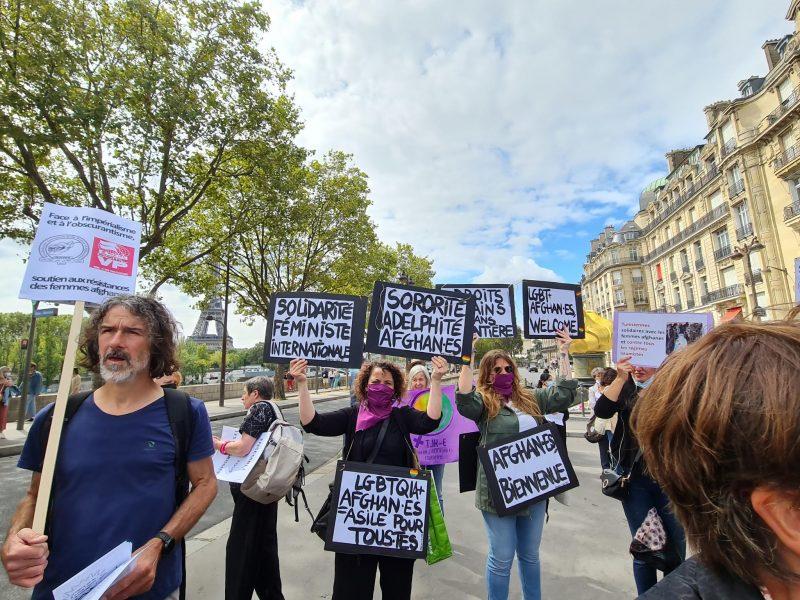 militantes avec pancartes sororité adelphité afhganes LGBTQI+ afghan.es = asile pour tous.tes Afhganes bien venue welcome